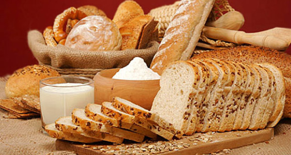 Assortment of baked breads with yoghurt and a bowl of flour on red background